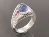 Sapphire ring with diamond and ruby side stones.